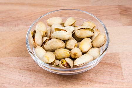 Pistachios on bowl on a beech wood table