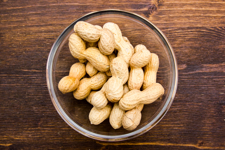 Peanuts on bowl on a wooden table viewed from above