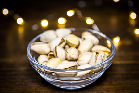 Pistachios on bowl on a wooden table with blurred lights in the background