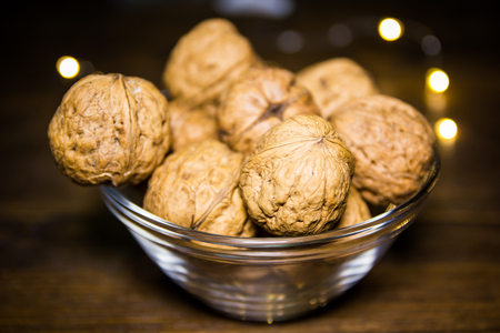 Walnuts on bowl on a wooden table with blurred lights in the background 免版税图像