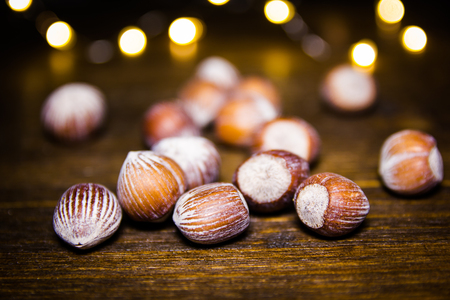 Hazelnuts on a wooden table with blurred lights in the background 免版税图像