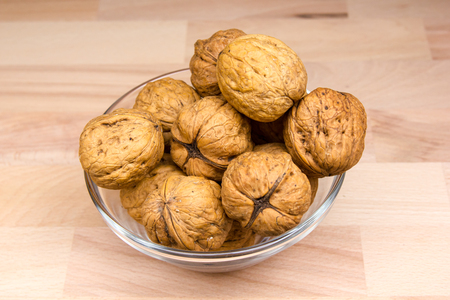 Walnuts on bowl on a beech wood table Banque d'images