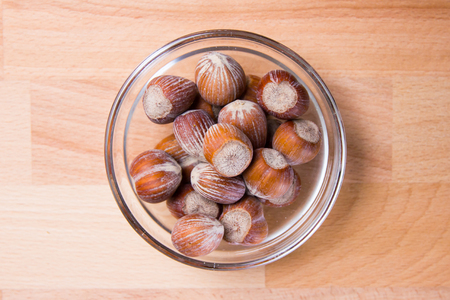 Hazelnuts on a bowl on a beech wood table viewed from above
