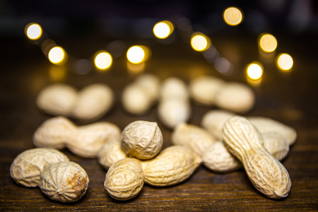 Peanuts on a wooden table with blurred lights