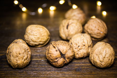 Walnuts on a wooden table with blurred lights in the background