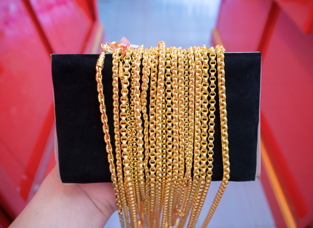 Gold necklaces jewelry hold by hand Imagens