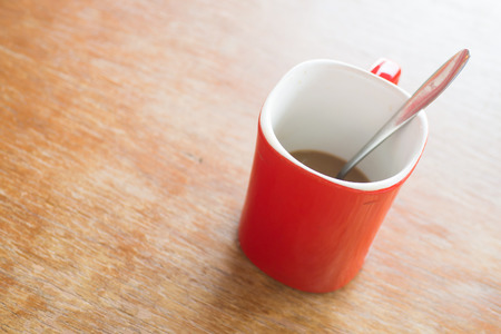 Hot coffee in red cup with long spoon copy space