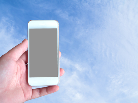 Left-hand holds the smartphone grey screen with sky background behind