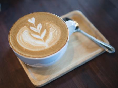 Hete koffie grote cappuccino-kop met zilveren lepel op het houten dienblad en de donkere lijst