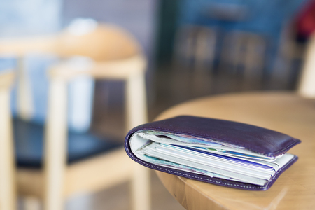 Selective focus on wallet style on the table in coffee shop blurry background