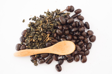 Coffee bean and tea leaves with wood spoon on white background Imagens