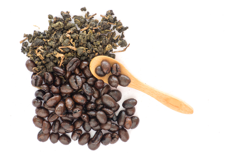 Coffee bean and tea leaves top view with wooden spoon on white background Imagens