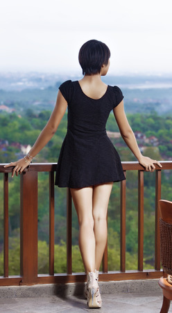 girl standing on the balcony, leaning his hands on the railing  dressed in black short dress  open legs, high heels   against the backdrop of the island and the bay photo