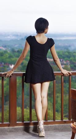 gambe aperte: ragazza in piedi sul balcone, appoggiando le mani sulla ringhiera vestita di nero vestito corto gambe aperte, tacchi alti sullo sfondo dell'isola e sulla baia