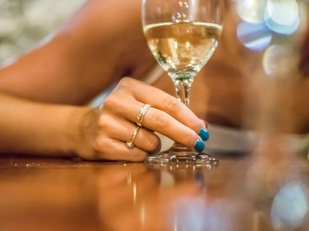 Woman hand holding glass of white wine