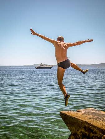 Heureux, jeune homme sautant dans l'eau. Banque d'images - 34774026