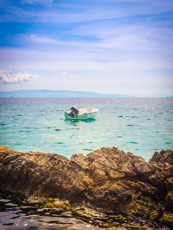 Boat floating on the calm waves Adriatic photo