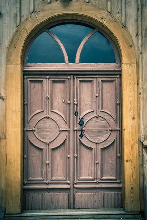 semicircular: Old wooden semicircular front door in an old church