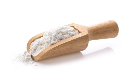 Pile of flour in wood scoop isolated on white background.