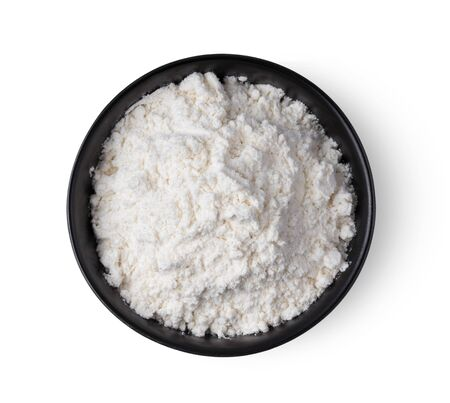 Pile of flour in black bowl isolated on white background. top view Stock Photo