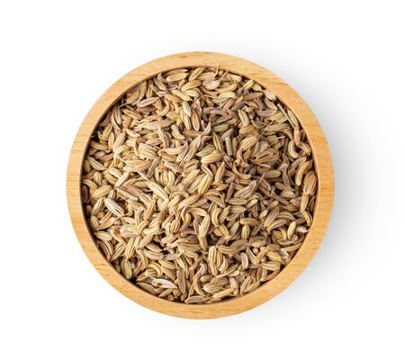 fennel seeds in wood bowl on white background. top view