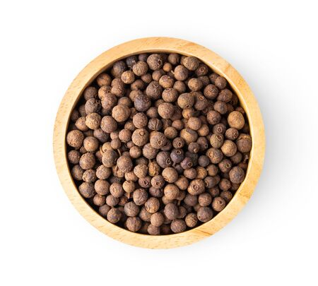 Allspice berries (also called Jamaican pepper or newspice) in wood bowl on white background. top view