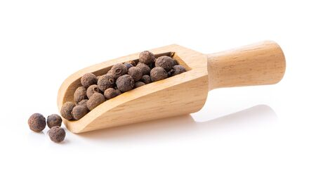 Allspice berries (also called Jamaican pepper or newspice) in wood scoop over white background