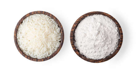 rice grains and pile of flour in wood bowl isolated on white background. Top view