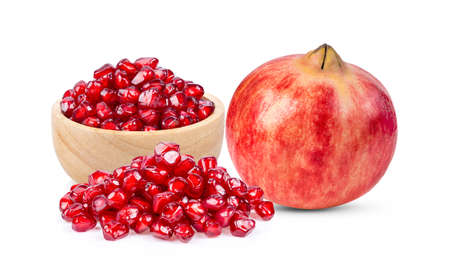 Pomegranate seeds in wood bowl isolated on white background Foto de archivo