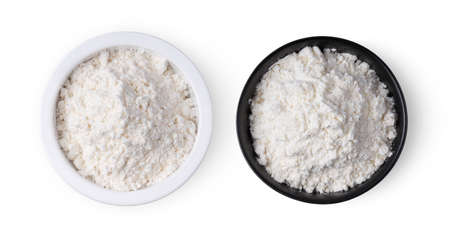 Pile of flour in a bowl isolated on white background. top view