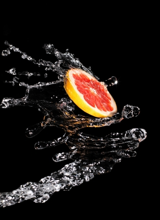 Slice grapefruit in a large drop of clear water Stock Photo