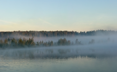 Fog over the lake shore in the sky and the forest cool autumn morning photo