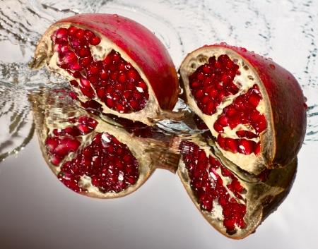 Two slices of ruby pomegranate in water jet reflected in a mirror surface Stock Photo