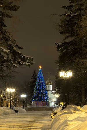 Winter city alley leading to the church and decorated the Christmas tree photo