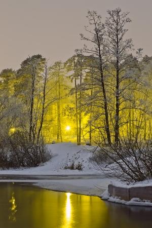 Зимняя река на фоне ночного города огней отражаются в воде