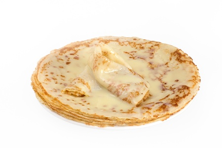 pancake week: Fried round pancakes with condensed milk on a saucer on a white background