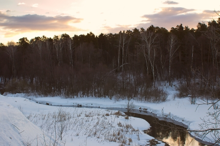 gold en: Pehorka river in a dark forest and bright clouds illuminated setting sun