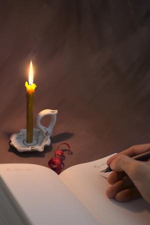 Рука с ручкой отпуск гостевая освещенном пламенем горящей свечи