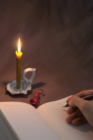 book reviews: Hand with pen leave guestbook lit flame burning candle