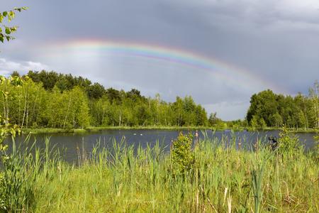 Летняя радуга после сильного дождя на озере Фото со стока