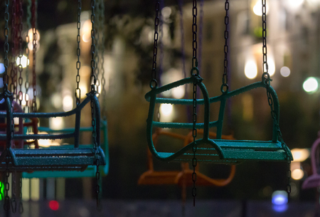 Empty wet swing on the background lights of the night city Фото со стока - 92703061