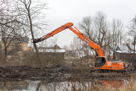 Balashikha, Moscow region - November 24, 2017: Cleaning of the Malashka river bed of the left tributary of the Pekhorka River from silt, debris and shrubs