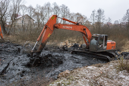 Balashikha, Moscow, Russia - November 28, 2017: Cleaning the riverbed of the river Malashka, left tributary Pehorka river of silt, mud, bushes and shrubs Редакционное