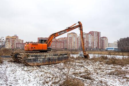 Balashikha, Moscow region, Russia - November 29, 2017: Transportation of a floating excavator to the bank of the river Pekhorka for cleaning the riverbed