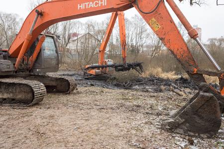 Balashikha, Moscow region, Russia - November 29, 2017: Working excavators on the bank of the Malashka river near Nikolskaya street, deepening the river bottom