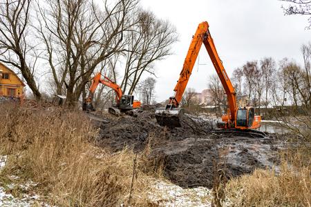 Balashikha, Moscow region, Russia - November 30, 2017: Working excavators on the bank of the Malashka river in the Nikolsky street area, deepening the river bottom Редакционное