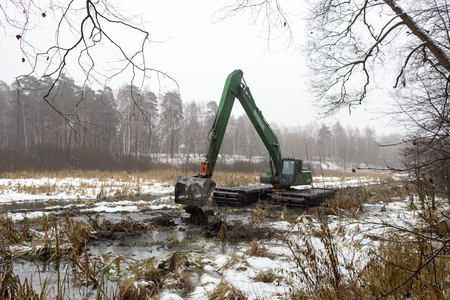 Balashikha, Moscow region, Russia - December 04, 2017: Floating excavator cleans the riverbed of the river Pekhorka from silt and debris