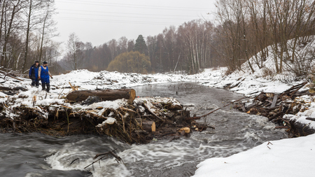 Balashikha, Moscow region, Russia - December 04, 2017: Workers dismantle the parts of the old bridge on the Pekhorka River in Pehra-Yakovlevskoye.