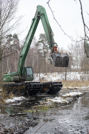 Balashikha, Moscow region, Russia - December 05, 2017: A floating excavator cleans the bottom of the Pekhorka River from mud and banks from the thickets Editorial
