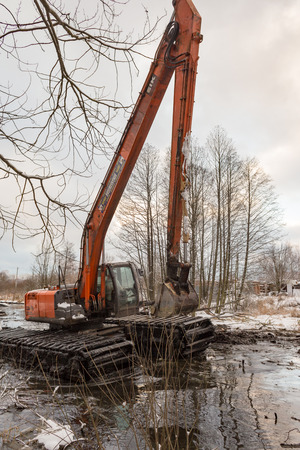 Balashikha, Moscow area, Russia - December 07, 2017: The excavator cleans the Malashka river bed from silt, dirt and thickets